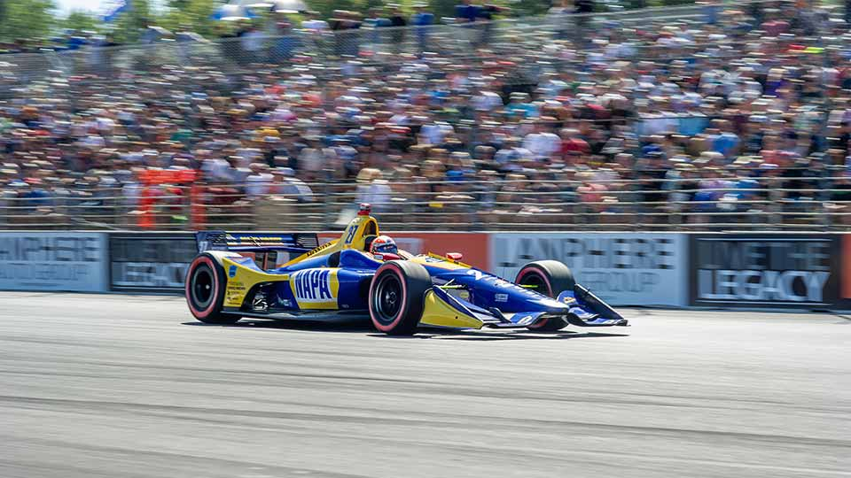 Alexander Rossi races by a full grandstand
